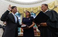 Mark Esper, left, is sworn in as the Secretary of Defense by Supreme Court Justice Samuel Alito, right, as is wife Leah Esper holds the Bible, during a ceremony with President Donald Trump in the Oval Office at the White House in Washington, on July 23, 2019. (AP Photo/Carolyn Kaster)