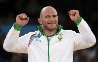 In this Aug. 11, 2012 file photo, gold medalist Artur Taymazov of Ukbekistan prepares to receive his medal during the victory ceremony for the men's 120-kg freestyle wrestling competition at the 2012 Summer Olympics, in London. (AP Photo/Paul Sancya)