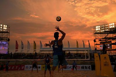 五輪会場でのテストを兼ね開かれたビーチバレーボールの国際大会で、赤く染まった夕焼けの空に向かってサーブを打つ選手=東京都品川区の潮風公園で、手塚耕一郎撮影