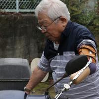 バイクに乗るときはハンドル左側に義手を引っかけ、ブレーキを操作している=大阪府池田市で、小出洋平撮影