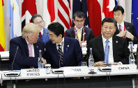 U.S. President Donald Trump, left, shakes hands with Japanese Prime Minister Shinzo Abe next to Chinese President Xi Jinping, seated at right, after a special event at the G-20 summit in Osaka, on June 28, 2019. (Pool photo)
