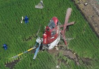 The helicopter that crashed in the Ibaraki Prefecture city of Chikusei is seen at 9:44 a.m. on July 29, 2019, a little over an hour after it crashed as it was crop dusting, in this photo taken from a Mainichi Shimbun helicopter. (Mainichi/Kimi Takeuchi)