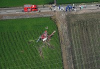 The helicopter that crashed in the Ibaraki Prefecture city of Chikusei is seen at 9:36 a.m. on July 29, 2019, with a power line nearby, in this photo taken from a Mainichi Shimbun helicopter. (Mainichi/Kimi Takeuchi)