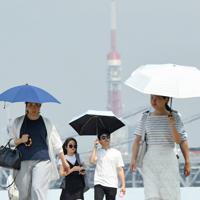 朝から強い日差しとなる中を歩く人たち=東京・台場で2019年7月29日午前9時49分、丸山博撮影