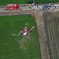 農薬散布をしていて水田に墜落したヘリコプター。近くには送電線も見える=茨城県筑西市で2019年7月29日午前9時36分、本社ヘリから竹内紀臣撮影