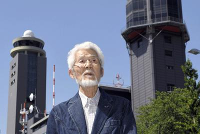 成田空港の旧管制塔(右)と現在の管制塔の前で、開港当時を振り返る故柴田謙二さん=千葉県成田市で2018年5月