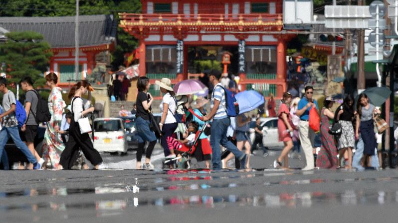 強い日差しで「逃げ水」現象が見られる中、横断歩道を渡る人たち=京都市東山区で2018年