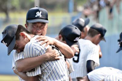泣きながら喜びを分かち合う明徳義塾の選手たち=高知市春野町の県立春野球場で、北村栞撮影