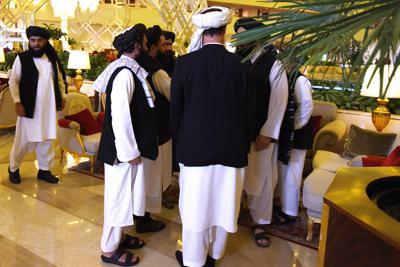 当事者間対話の前に話し込むタリバンのメンバー=ドーハで2019年7月8日、松井聡撮影