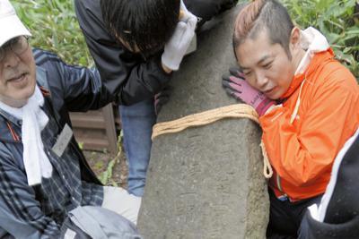 倒れた墓石を起こしてモルタルで土台に固定する訪問団員=択捉島の紗那墓地で、井桁正美さん提供