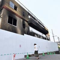 放火殺人事件現場となった「京都アニメーション」第1スタジオの前に立ち尽くす女性。1日には安全対策として窓をシートで覆う工事が行われた=京都市伏見区で2019年8月1日午後3時24分、川平愛撮影