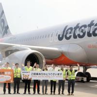 庄内行きの初便の前で手を振るジェットスター・ジャパンのスタッフ=成田空港で