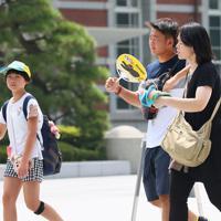 朝から厳しい暑さの中、うちわであおぎながら歩く人たち=東京都千代田区で2019年8月2日午前10時28分、吉田航太撮影