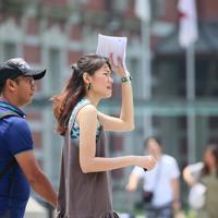 朝から厳しい暑さの中、日差しを遮りながら歩く女性=東京都千代田区で2019年8月2日午前11時6分、吉田航太撮影