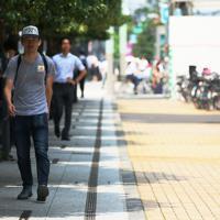 強い日差しを避けて日陰を歩く人たち=東京都中央区で2019年8月2日午前9時42分、吉田航太撮影