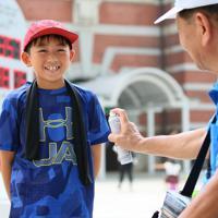 朝から厳しい暑さの中、冷却スプレーで涼み、気持ちよさそうな子ども=東京都千代田区で2019年8月2日午前10時21分、吉田航太撮影