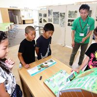 がけ崩れの仕組みを模型で学ぶ三百瀬小学校の児童ら=和歌山県日高川町小熊で、山本芳博撮影
