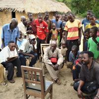 森林調査時にコンゴ民主共和国の環境省職員が持参したパソコンの画像を熱心に眺める村の住民(同省提供)