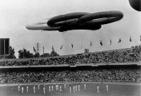 1968 Mexico City Olympics -- Balloons representing the five Olympic rings float in the sky over the stadium during the opening ceremony. A total of 112 nations and regions participated in the global event.