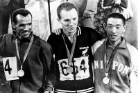 1968 Mexico City Olympics -- Japan's Kenji Kimihara, right, smiles as he receives the silver medal during the award ceremony for the men's marathon. Mamo Wolde of Ethiopia, left, won the gold, while Mike Ryan, of New Zealand, center took the bronze.