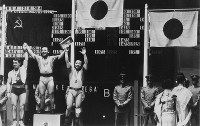 1968 Mexico City Olympics -- Japan's Yoshinobu Miyake, who won the gold, and his younger brother Yoshiyuki, who took the bronze, celebrate together at the medal ceremony of the featherweight division in men's weightlifting.