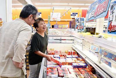 4割引きになった箱アイスを選ぶ夫婦=金沢市の大阪屋ショップ近岡店で、日向梓撮影