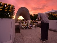 A man prays for the victims of the Aug. 6, 1945 U.S. atomic bombing of Hiroshima in front of the Cenotaph for the A-bomb Victims at Peace Memorial Park in Hiroshima's Naka Ward at dawn on Aug. 6, 2019. (Mainichi/Naohiro Yamada)