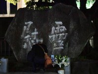A person prays for the victims of the Aug. 6, 1945 U.S. atomic bombing of Hiroshima in front of a cenotaph beside the A-Bomb Dome at Peace Memorial Park in Hiroshima's Naka Ward at dawn on Aug. 6, 2019. (Mainichi/Yoshiyuki Hirakawa)