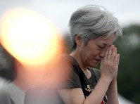 A woman prays for the victims of the atomic bombing of Hiroshima in front of the Cenotaph for the A-bomb Victims at Peace Memorial Park in Hiroshima's Naka Ward early in the morning on Aug. 6, 2019. (Mainichi/Naohiro Yamada)