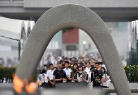 People pray for the victims of the atomic bombing of Hiroshima in front of the Cenotaph for the A-bomb Victims at Peace Memorial Park in Hiroshima's Naka Ward early in the morning on Aug. 6, 2019. (Mainichi/Kenji Ikai)