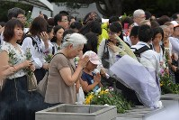 People offer flowers in front of the Cenotaph for the A-bomb Victims at Peace Memorial Park in Hiroshima's Naka Ward early in the morning on Aug. 6, 2019. (Mainichi/Yoshiyuki Hirakawa)