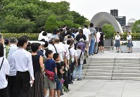 Many people form a line to offer flowers in front of the Cenotaph for the A-bomb Victims at Peace Memorial Park in Hiroshima's Naka Ward early in the morning on Aug. 6, 2019. (Mainichi/Yoshiyuki Hirakawa)