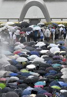 People form a line in front of the Cenotaph for the A-bomb Victims while holding umbrellas amid rain at Peace Memorial Park in Hiroshima's Naka Ward on Aug. 6, 2019. (Mainichi/Naohiro Yamada)
