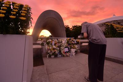 朝焼けの中、原爆慰霊碑の前で犠牲者の冥福を祈る男性=広島市中区の平和記念公園で2019年8月6日午前5時15分、山田尚弘撮影