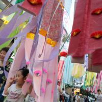 仙台七夕まつりが開幕し、商店街につり下げられた吹き流しと共に記念撮影する人たち=仙台市で2019年8月6日午後6時28分、和田大典撮影