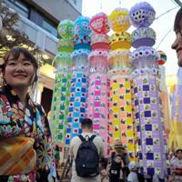 仙台七夕まつりが開幕し、吹き流しが揺れる商店街を浴衣姿で散策する女性たち=仙台市で2019年8月6日午後6時39分、和田大典撮影