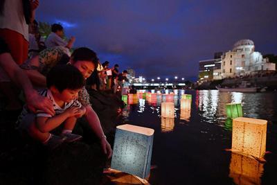 平和への祈りを込めて元安川に灯籠を流す人たち=広島市中区で2019年8月6日午後7時38分、猪飼健史撮影