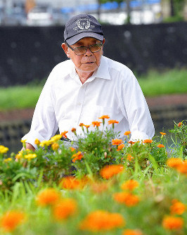 Hidetaka Komine is seen gazing at the flowerbed his friend Sanae Ikeda helped establish on the banks of the Urakami River, where many people died looking for water in the immediate aftermath of the atomic bombing, photographed in Nagasaki, Nagasaki Prefecture, on July 25, 2019. (Mainichi/Noriko Tokuno)