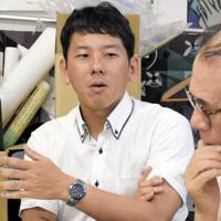 被爆者らと証言誌の内容を議論する山口響さん(左)=長崎市目覚町で、今野悠貴撮影