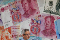In this Aug. 6, 2019 photo, a man walks by a money exchange shop decorated with Chinese yuan banknotes and other countries currency banknotes at Central, a business district in Hong Kong. (AP Photo/Kin Cheung)
