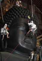 Cleaners beat the dust off the Great Buddha of Nara during an annual event at Todaiji temple in the city of Nara on Aug. 7, 2019. (Mainichi/Rei Kubo)