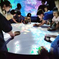「小人が住まうテーブル」に手を置いてみる子どもたち=鳥取県米子市の市美術館で、横井信洋撮影