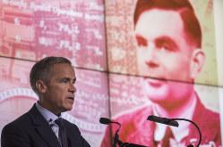 新50ポンドを発表したイングランド銀行のカーニー総裁。背景はチューリング氏の肖像(Bloomberg)