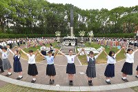 High school students are seen linking arms to form a chain around the Hypocenter Cenotaph, which marks the precise location that the atomic bomb was dropped, in Nagasaki on Aug. 9, 2019. (Mainichi/Noriko Tokuno)
