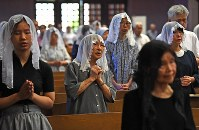 Worshippers are seen praying for peace and the victims of the atomic bombing during the morning Mass at Urakami Cathedral in Nagasaki on Aug. 9, 2019. (Mainichi/Tomohisa Yazu)