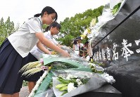 High school students are seen leaving flowers at the Hypocenter Cenotaph in Nagasaki on Aug. 9, 2019. (Mainichi/Noriko Tokuno)