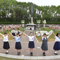 原爆落下中心地碑を囲むように人間の鎖を作る高校生たち=長崎市の爆心地公園で2019年8月9日午前7時4分、徳野仁子撮影