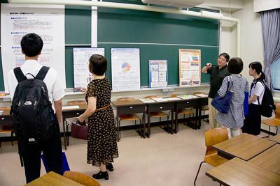 金沢大学のキャンパスビジットに参加し、地域創造学類福祉マネジメントコースのブースで教員から話を聞く高校生たち=眞鍋知子さん撮影