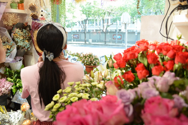 花を選ぶ女性。離婚後もDVと向き合う日々が続く=北京市海淀区で、浦松丈二撮影