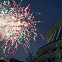 神宮外苑花火大会で打ち上げられた花火。右は建設中の新国立競技場=東京都新宿区で2019年8月10日午後7時32分、宮間俊樹撮影